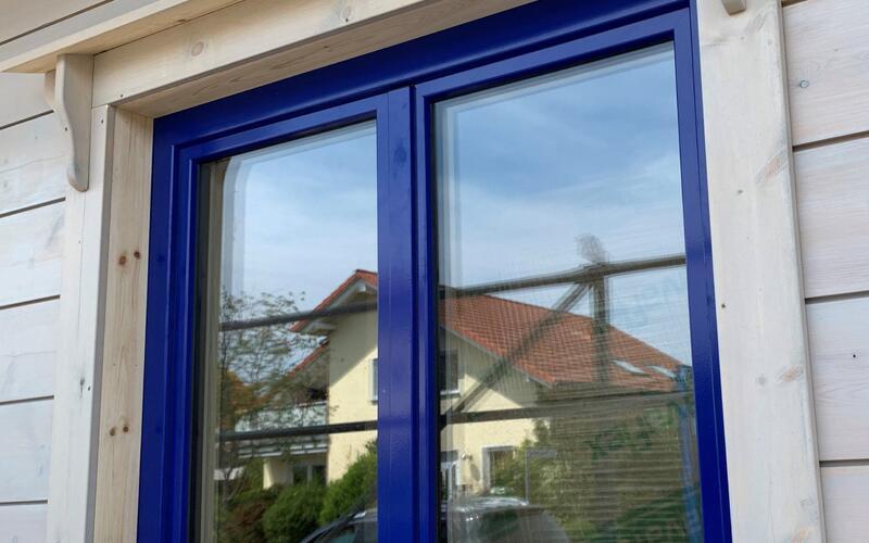 Attraktives Blockhaus mit blauen Fensterrahmen